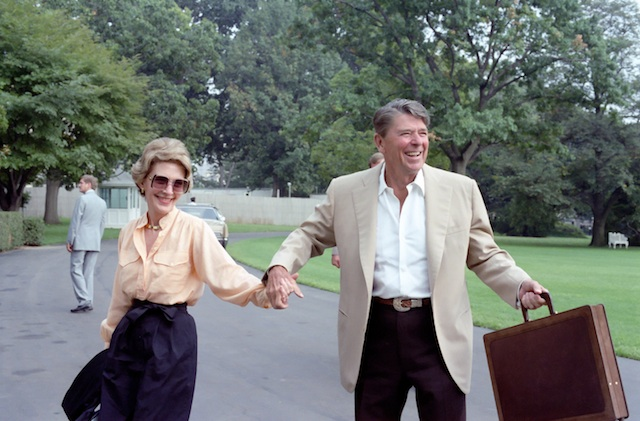 Ronald and Nancy Reagan holding hands and smiling at Camp David