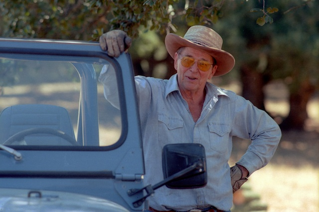 President Reagan at his Rancho Del Cielo in California, standing in casual wear with a cowboy hat, next to his blue jeep.