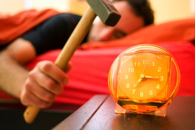 Man half asleep in be about to hit his ringing alarm clock with a hammer.