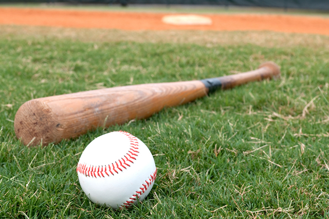 The change of landscaping in America. Photograpch of an old baseball bat with electrical tape around the grip, on the grass, next to baseball with home plate in the background