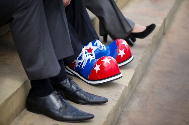 Image of the shoes of 3 different people, 1 of which is wearing clown shoes.