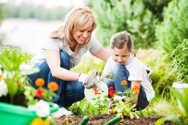 Smiling mother showing young daughter how to plant flowers