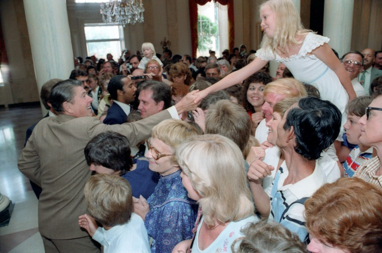 President Ronald Reagan shaking hands with visitors to the White House